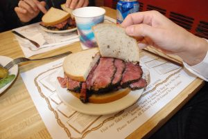 Couple Eating a Pastrami sandwich on a Restaurant