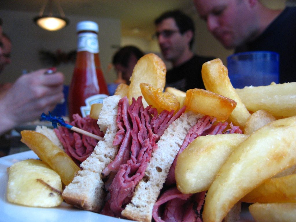 Family Eating Pastrami sandwich with Fries & Side Items