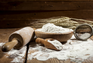 cake flour in a bowl and spilled on a table with rolling pin and scoop, with wheat in the backgound
