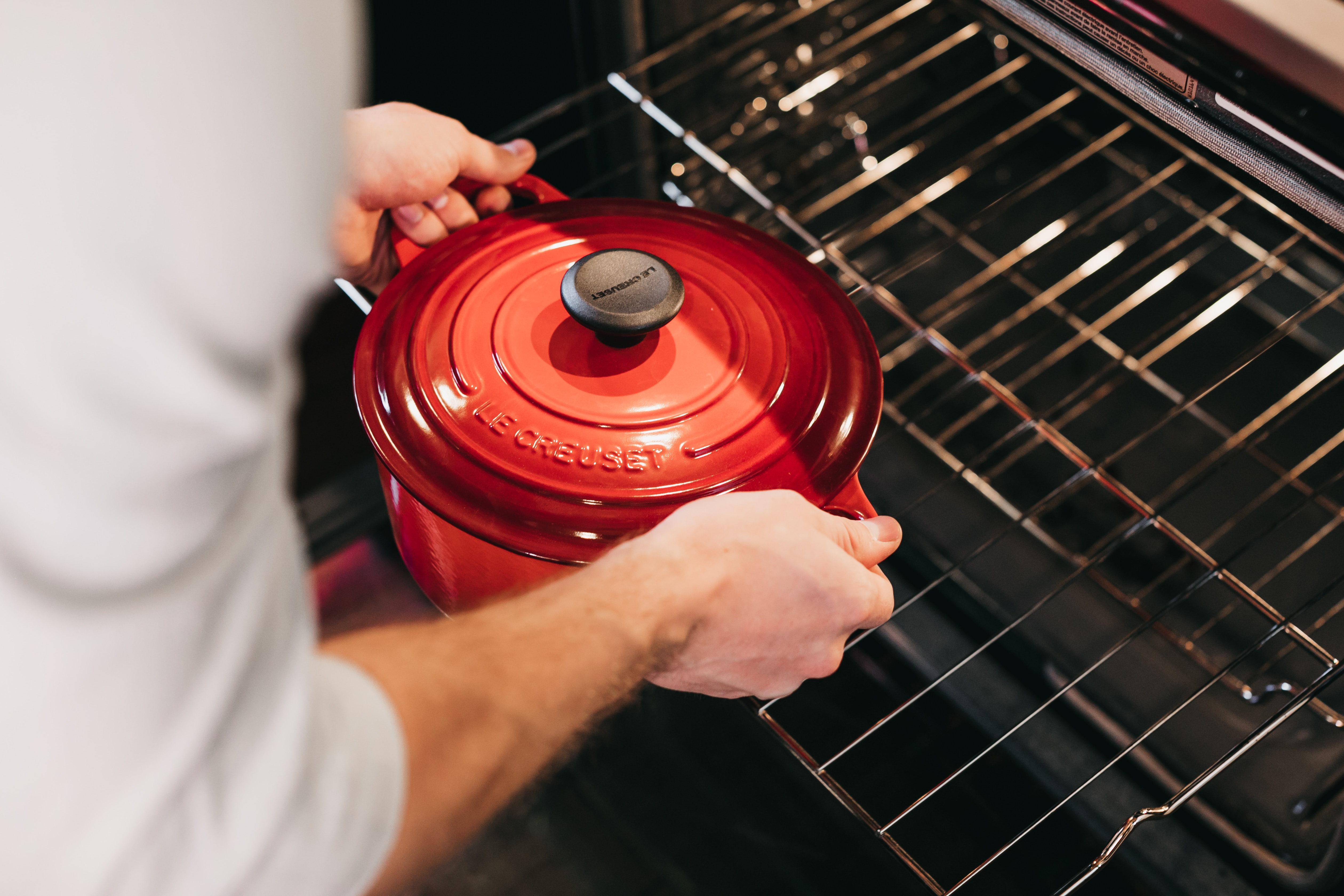 person holding red cook pot