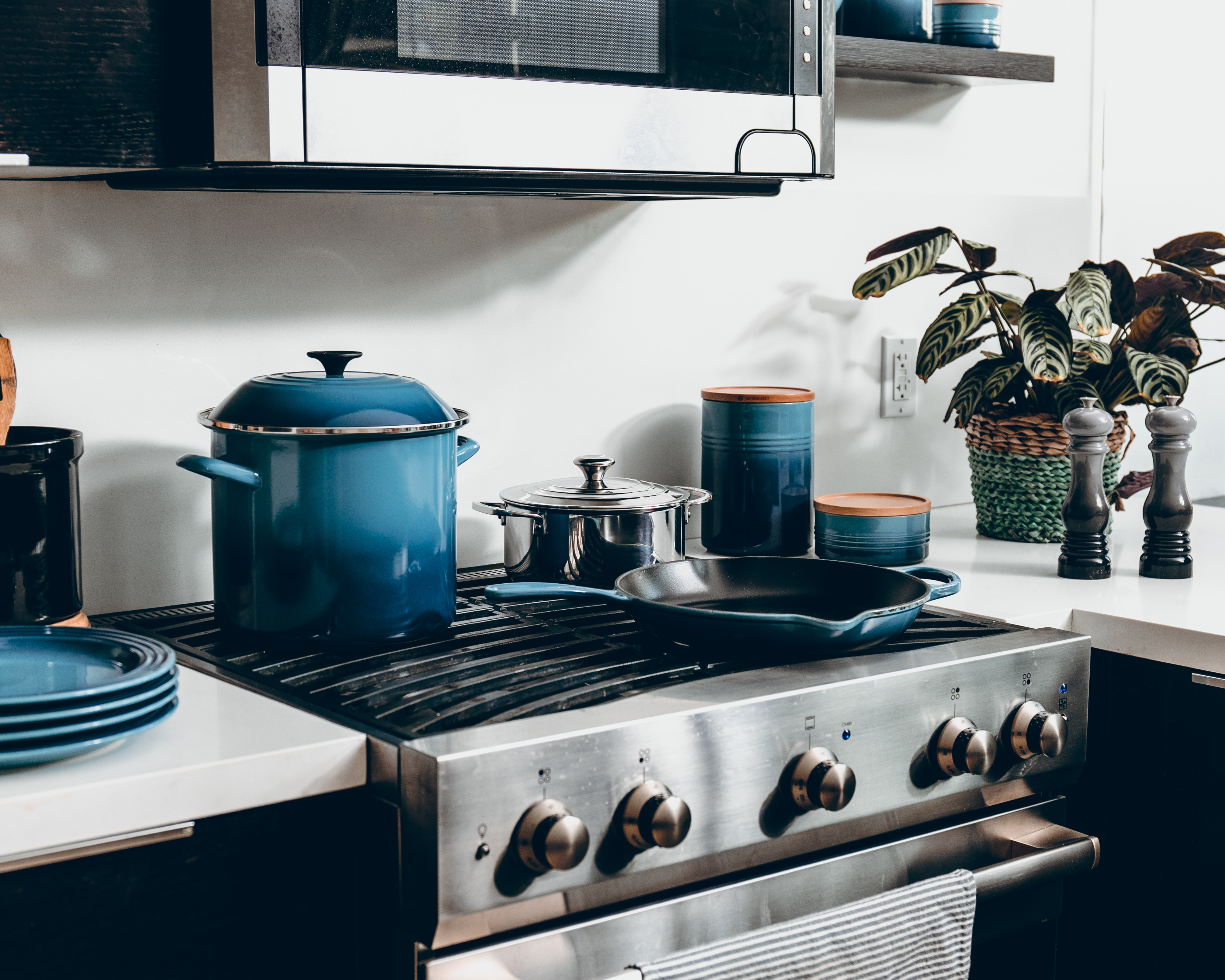 three blue canisters beside pan and plates