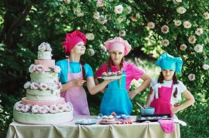three girls wearing colorful aprons show off their cake decorating skills