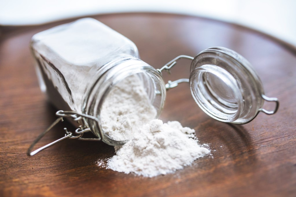flour spilling on the table from a glass jar