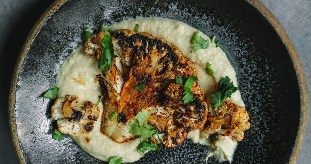 cooked cauliflower dish on a black plate